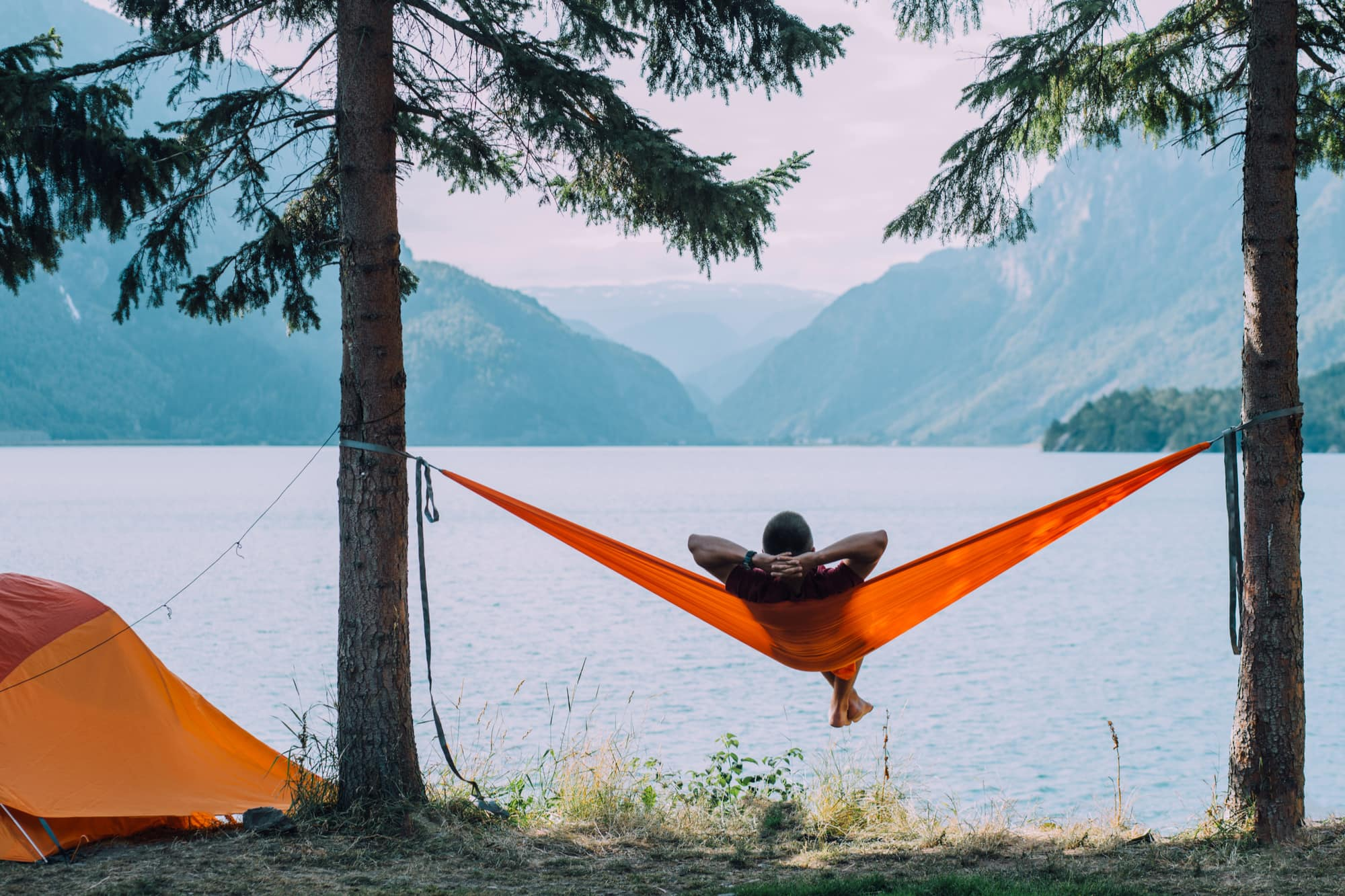 a man sitting in a hammock near a lake next to a tent