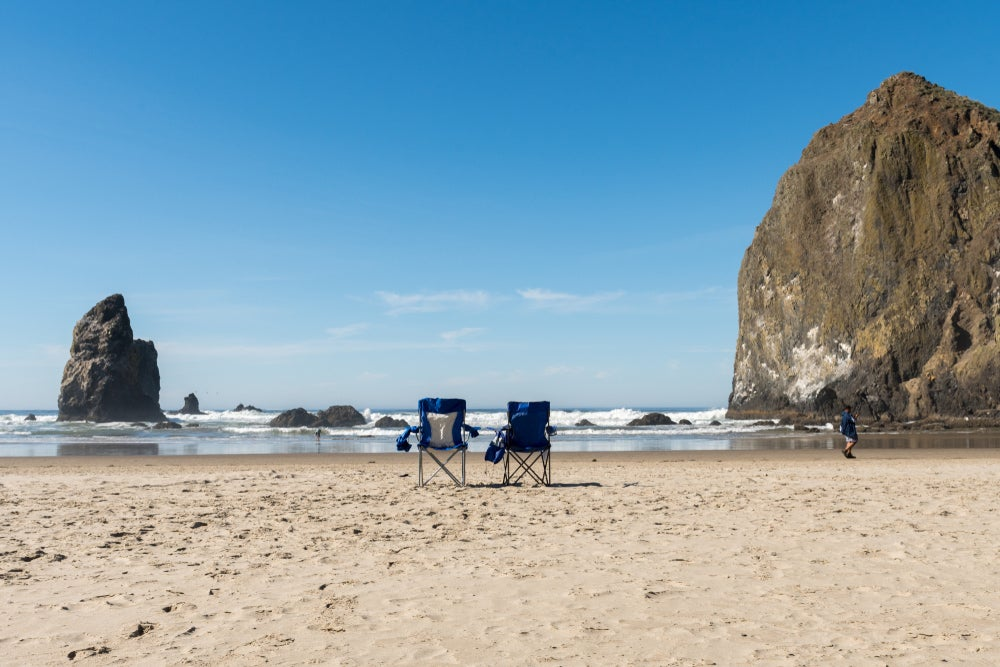 two beach chairs on the coast of oregon's cannon beach