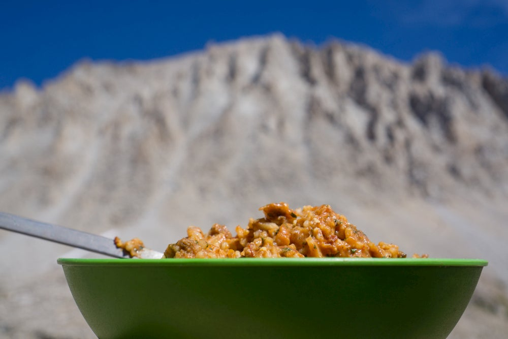 Camping meal in the foreground, mountain in the background.