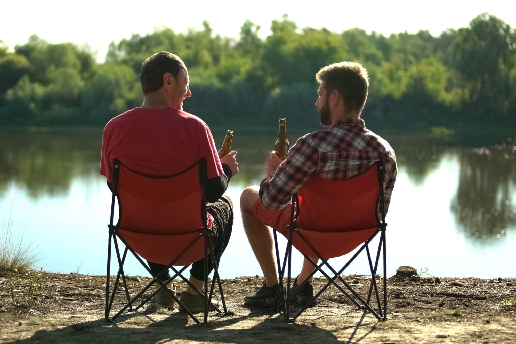two men sitting in camping folding chairs by a river