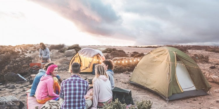 Group of friends on beach camping and eating dinner