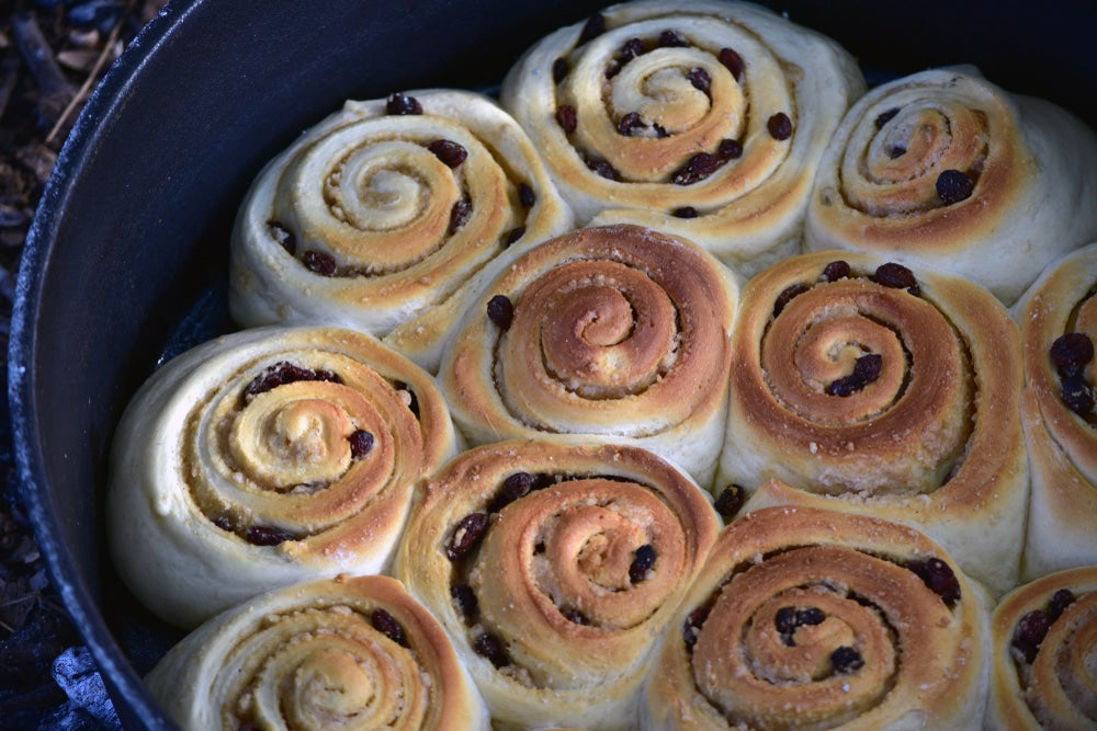 a bunch of cinnamon rolls in a dutch oven
