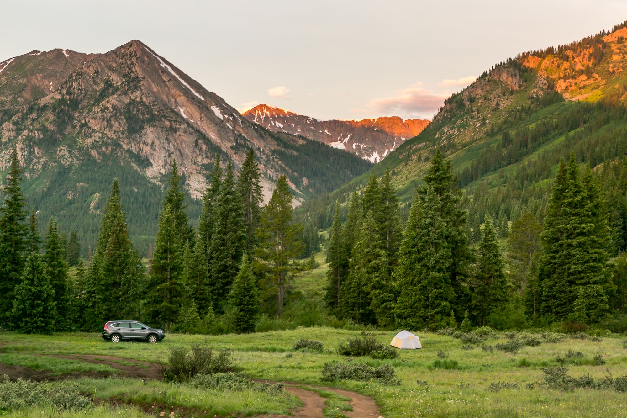 Car parked below rocky mountain range during alpenglow.