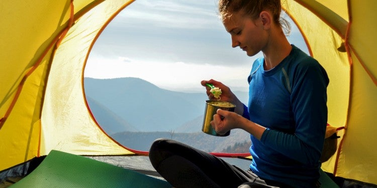 Female hiker eating food from a mug in her tent.