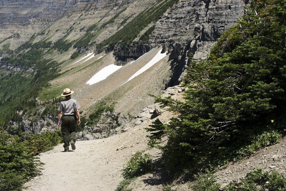 a park ranger hiking the highline trail in glacier national park, now closed due to bear activity.