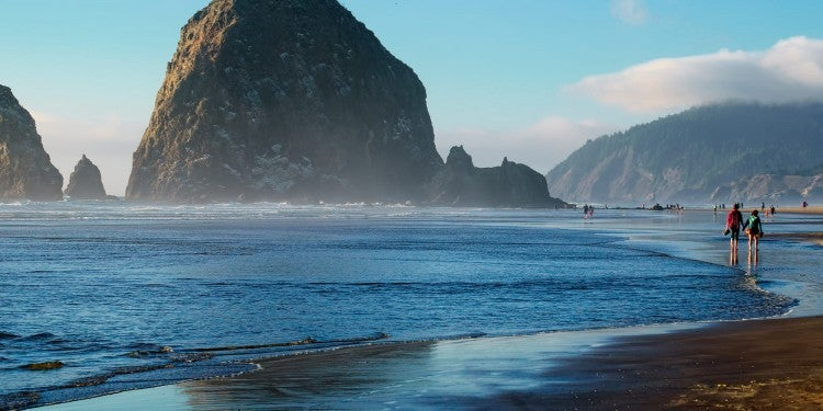 haystack rock in the water on the beach of cannon beach, oregon coast