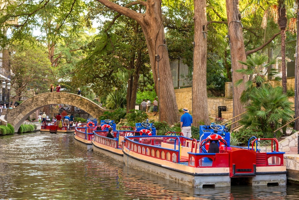 the san antonio riverwalk with boats in a line together