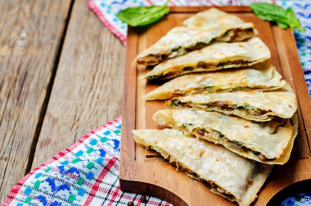 Mushroom quesadillas spread out on wooden platter.