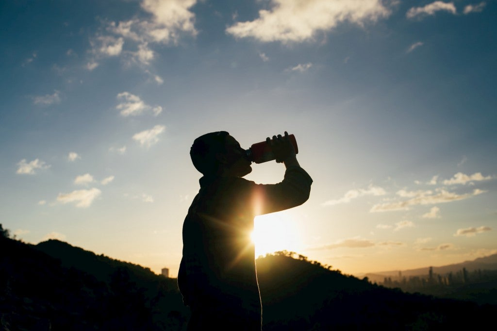 Silhouette of person drinking water during sunrise.