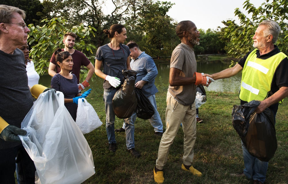 a group of volunteers in a field picking up garbage