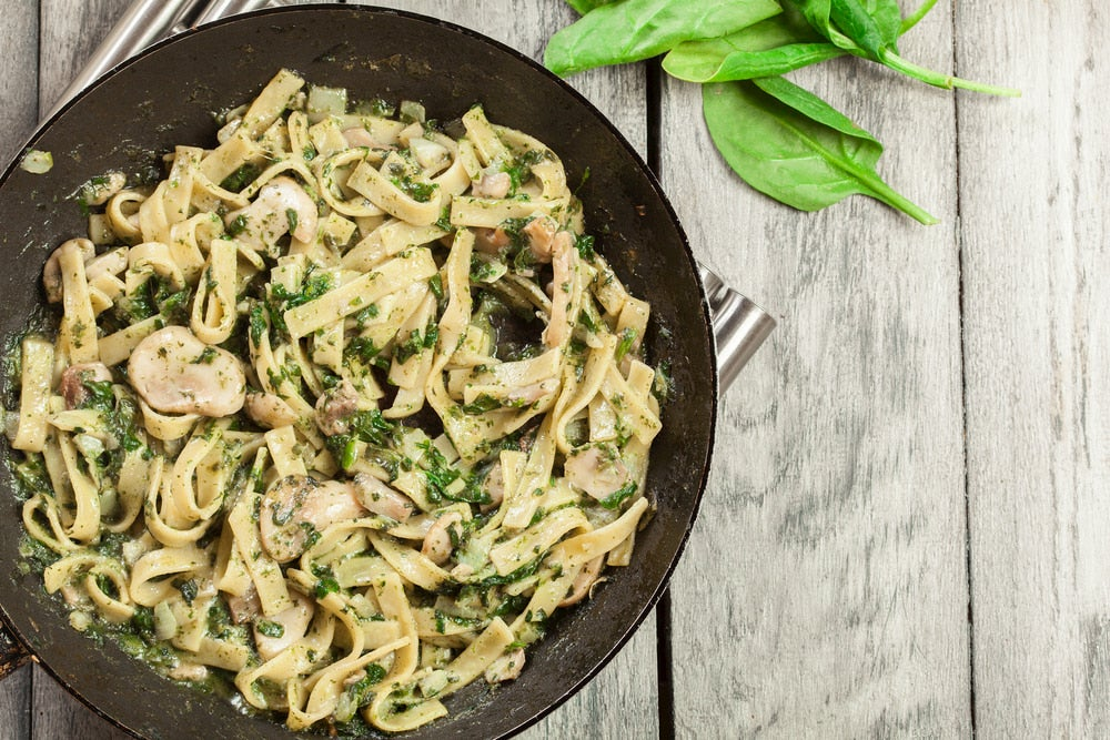 Creamy mushroom pasta garnished with basil leaves.