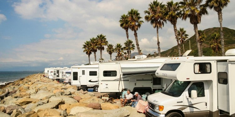 a row of RVs lined up on a beach