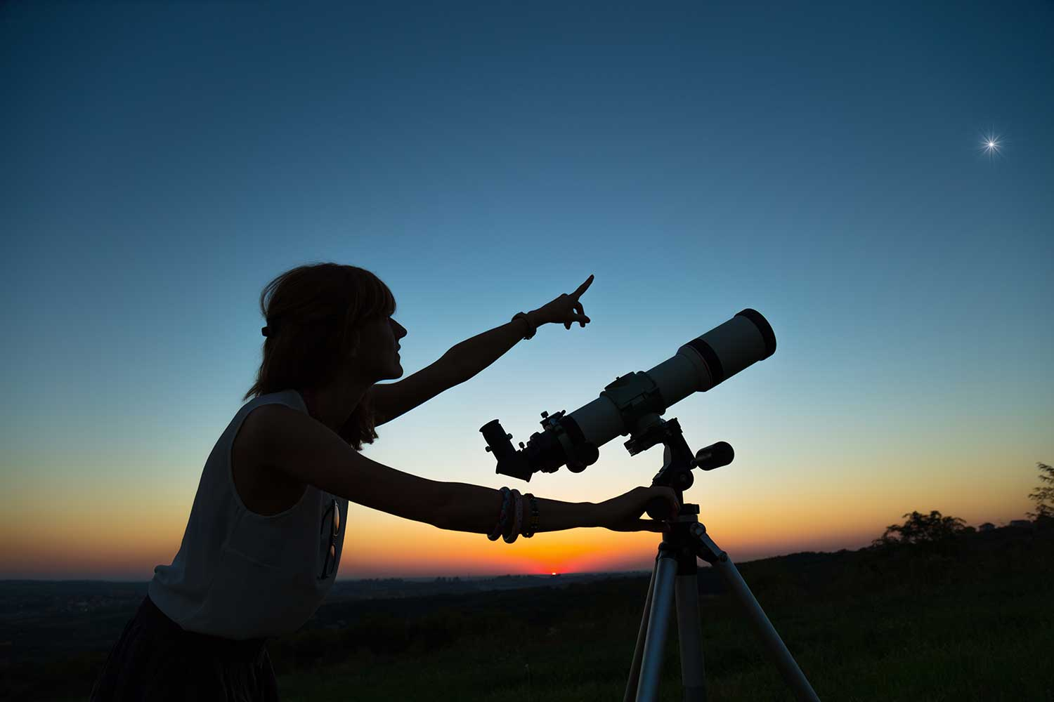 womans stands near telescope and points at a dark blue sky