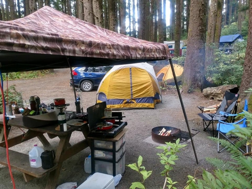 a tent and picnic table set up with camping gear near a forest