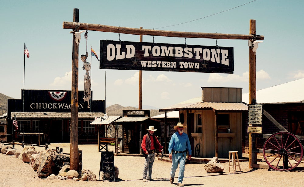 Two men walking under Old Tombstone sign in Arizona
