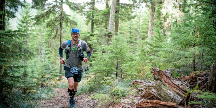 Mark Friess trail running through the woods in Hoka Evo Mafates.