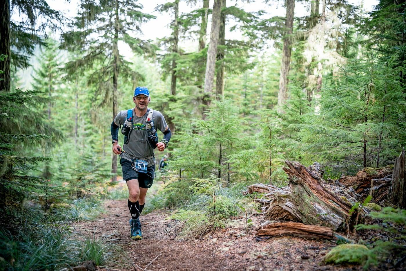Mark Friess trail running through the woods in Hoka Evo Mafates.