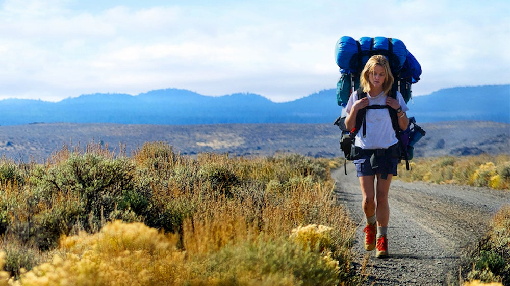 Cheryl Strayed hiking along dusty road with large backpack.