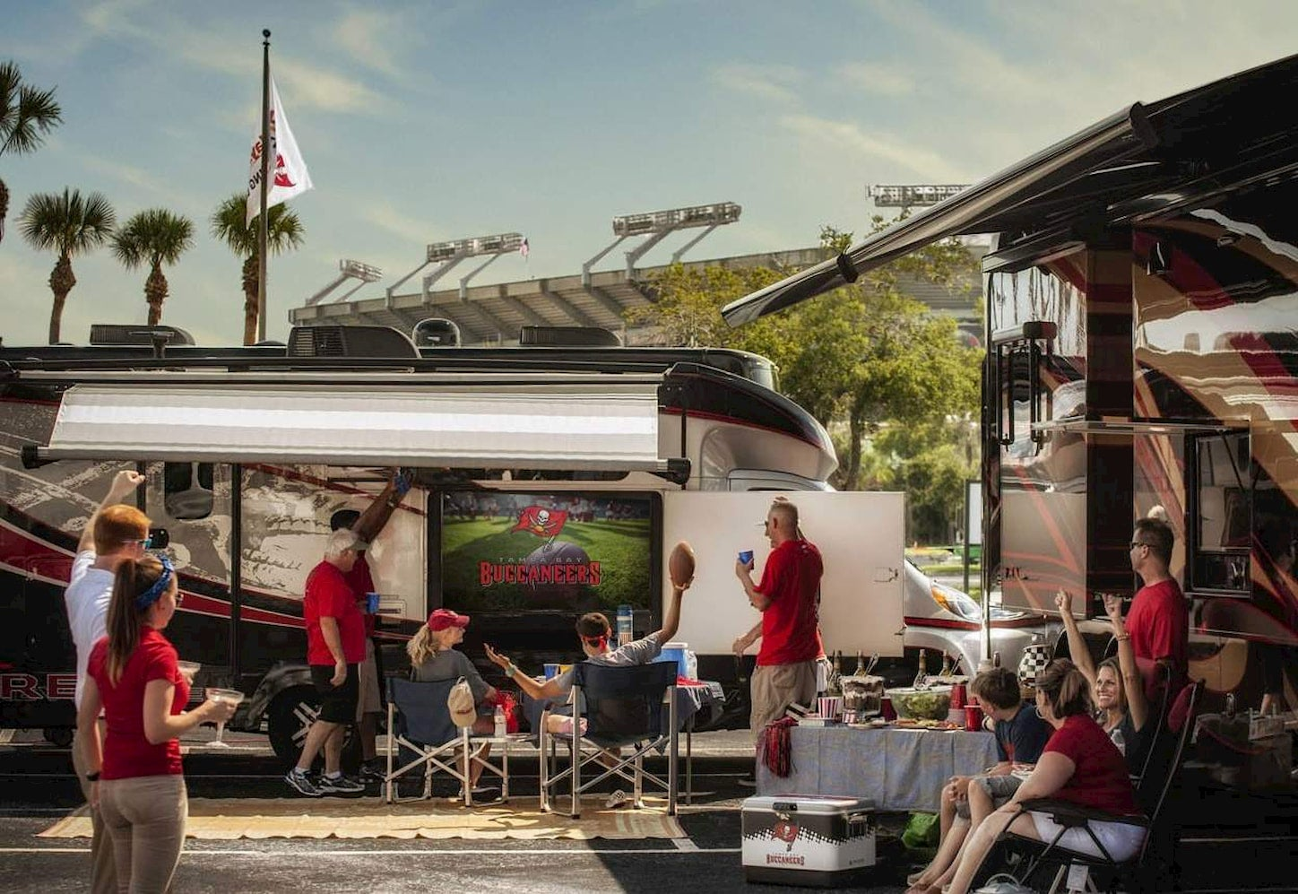 Group of tialgaters watching a t.v. in their RV outside of the stadium.