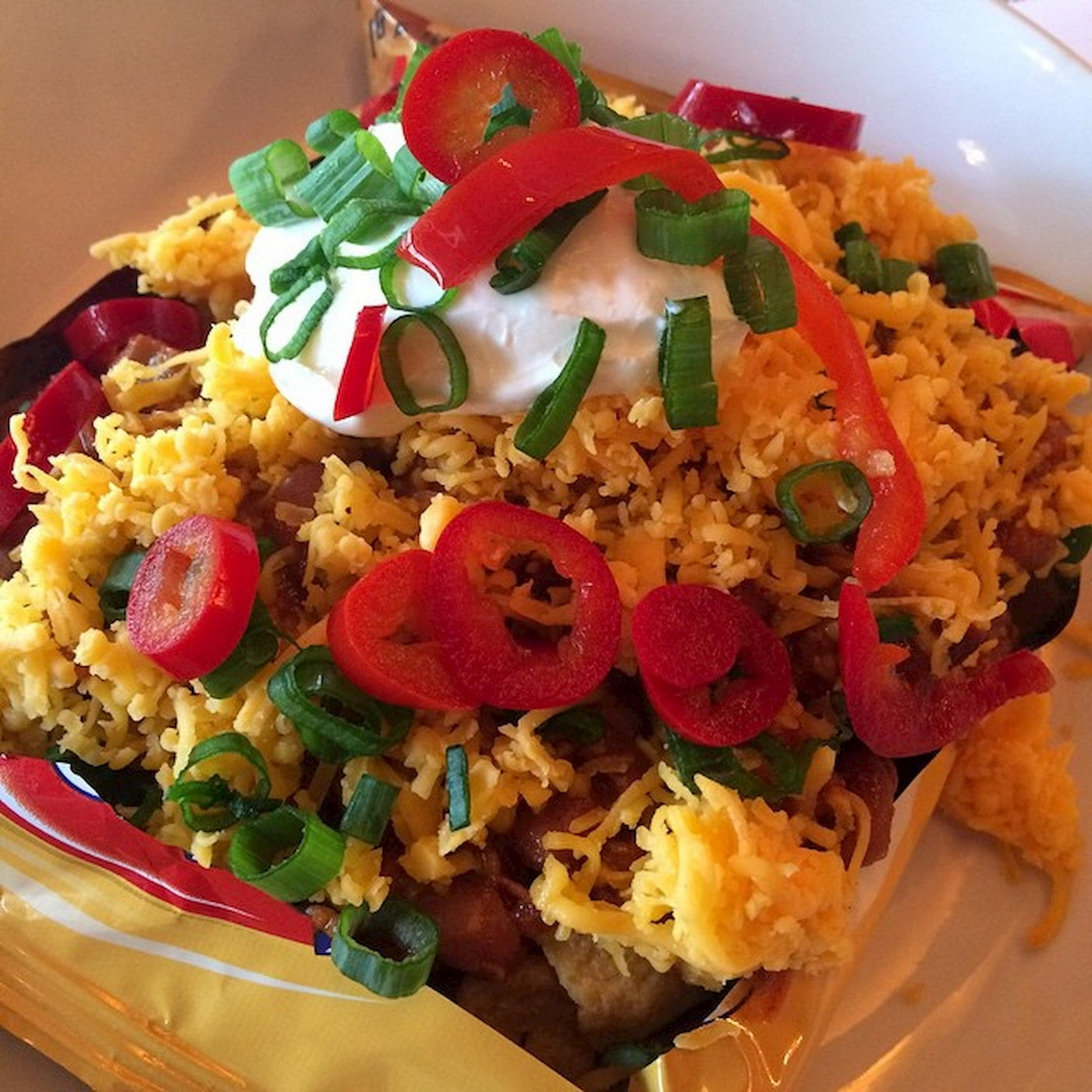 Frito pie with peppers and sour cream.