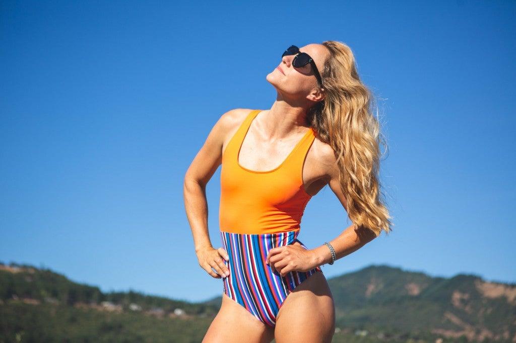 a woman posing in a one piece bikini in a desert