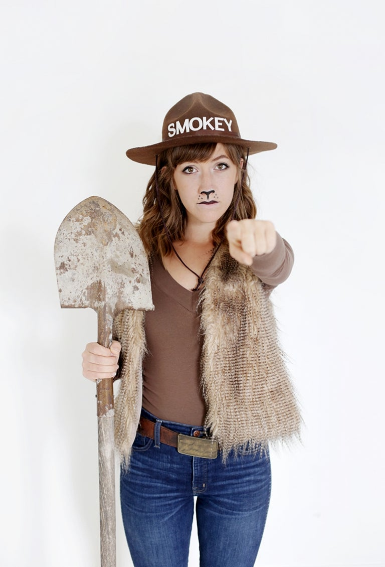 Girl in DIY smokey the bear costume with fur vest shovel.