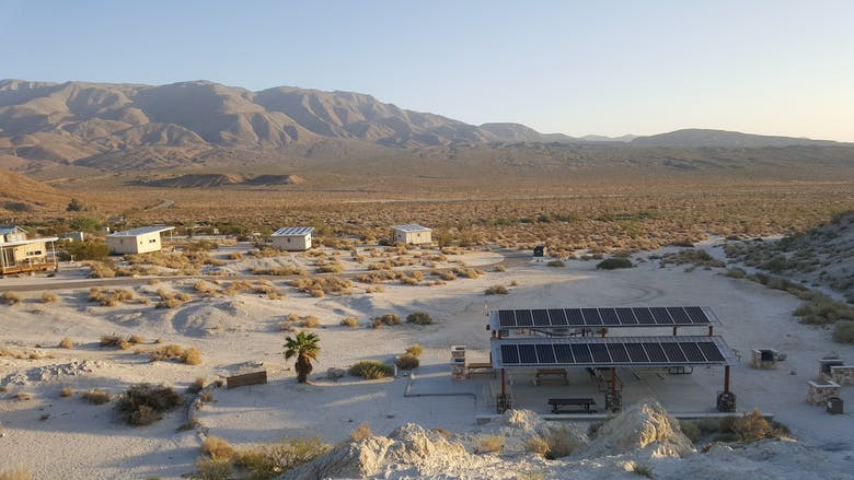 Arial view of desert park with solar panels and cabins