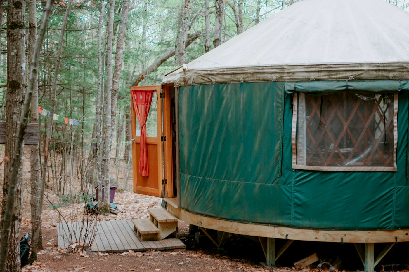 Green yurt with wooden steps up to it.