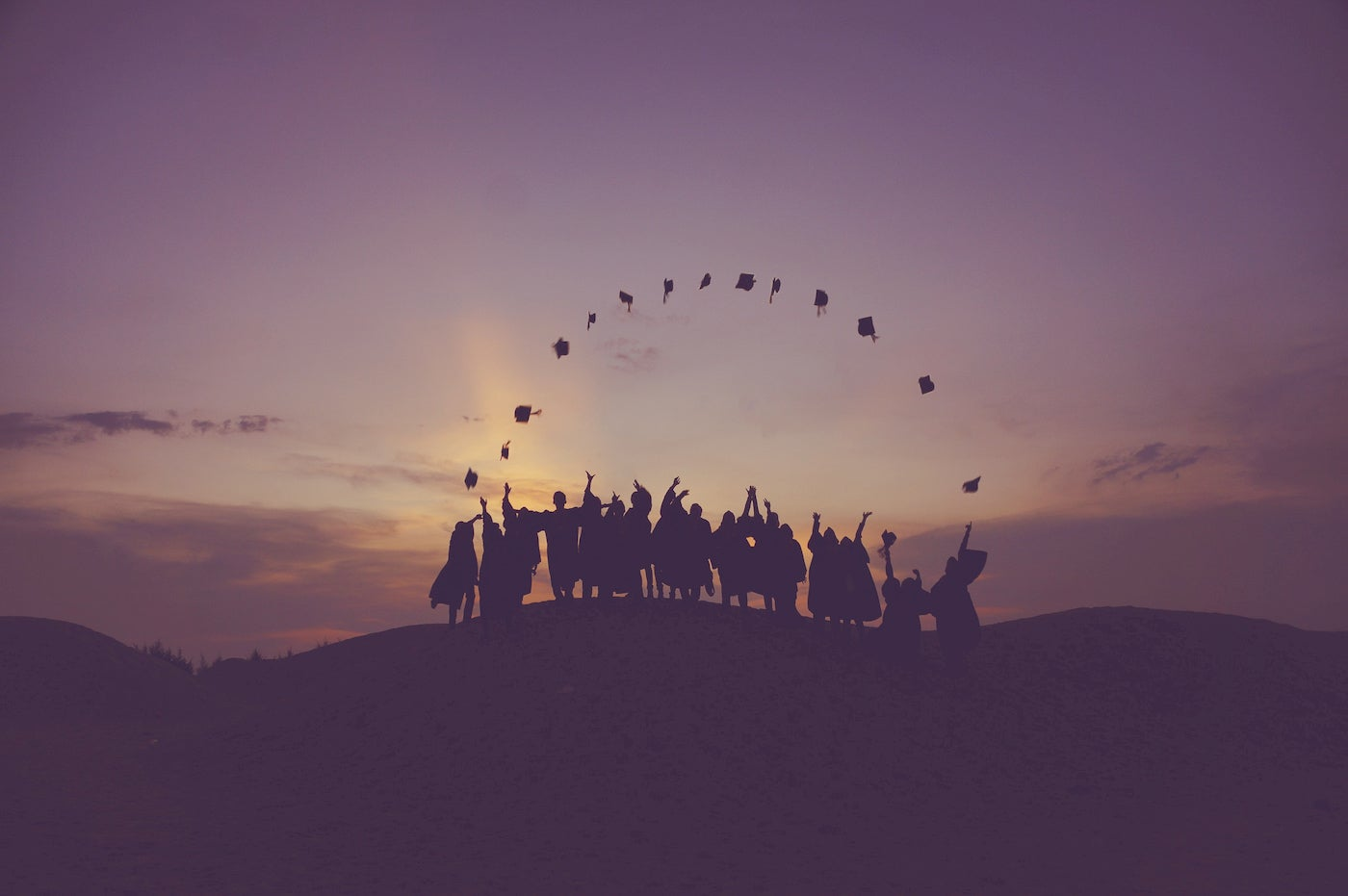 Silhouttes of graduates throwing their caps on a mountain.