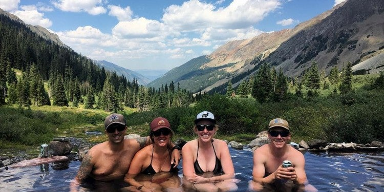 Group of four backpackers hanging out in hot springs.