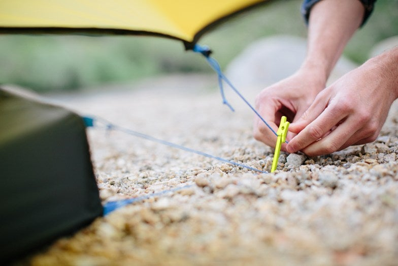 a person pinning down a tent to a tent stake in the ground