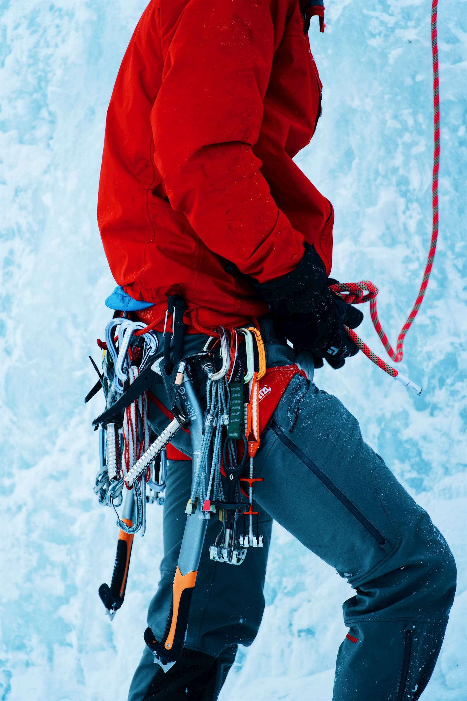 Ice climber with tons of trad gear, quick draws, and ice axes on their harness.