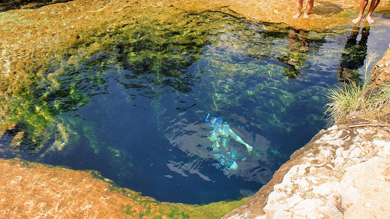 deep blue water of Jacob's well, swimmer submerged beneath the surface