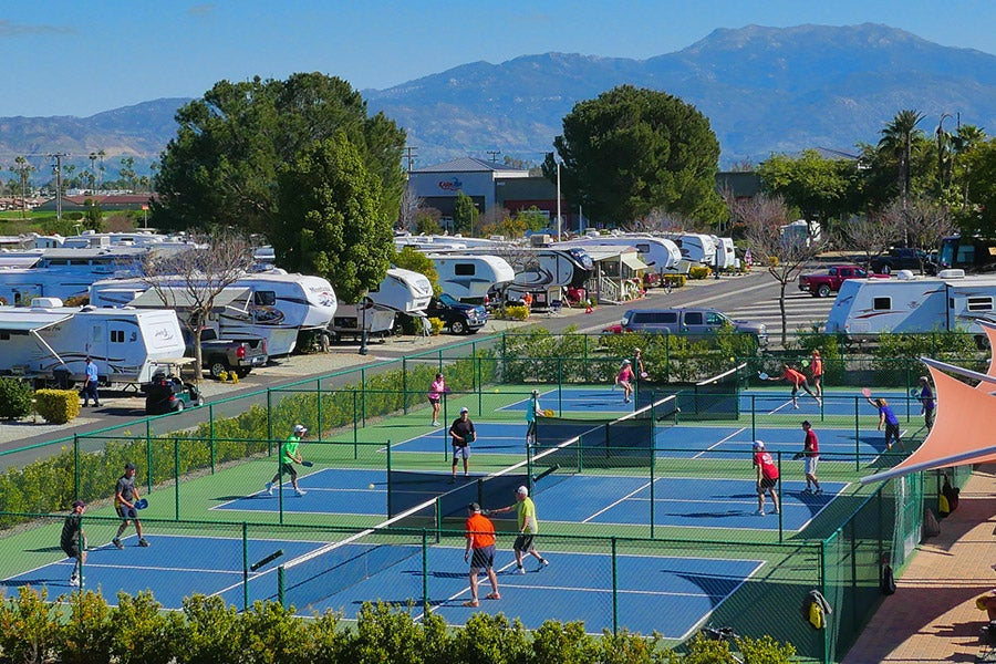 people playing pickleball in front of RV campers