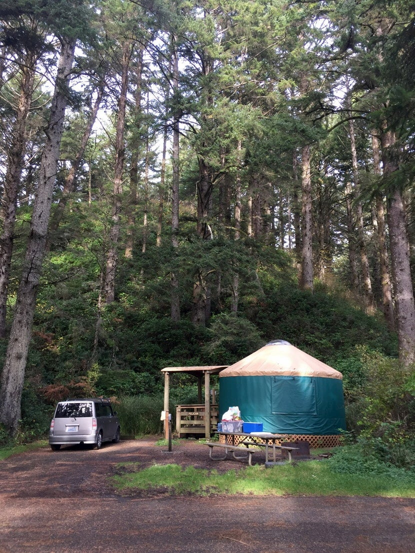 Oregon yurt in the woods beside a parked car.
