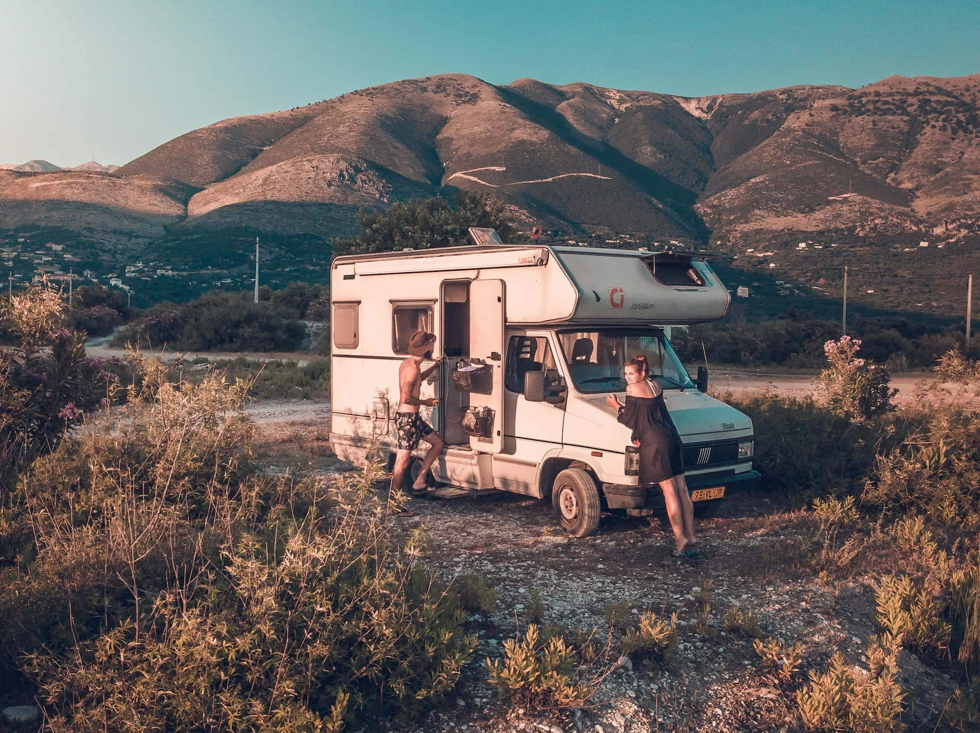 Young couple hanging outside their camper R.V. in a high alpine prairie.