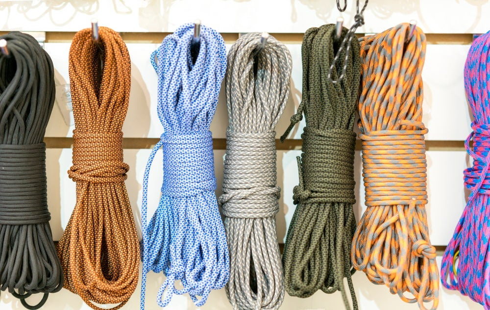 seven bundles of paracord strung up on racks in a store.
