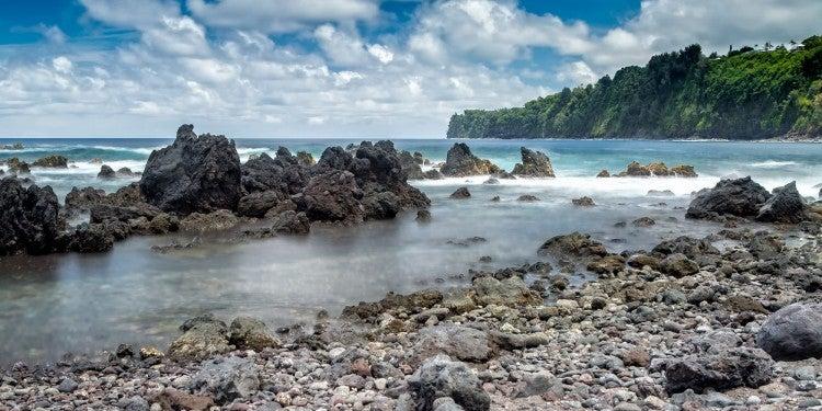 Waves breaking onto volcanic rocks on a Hawaiin beach.