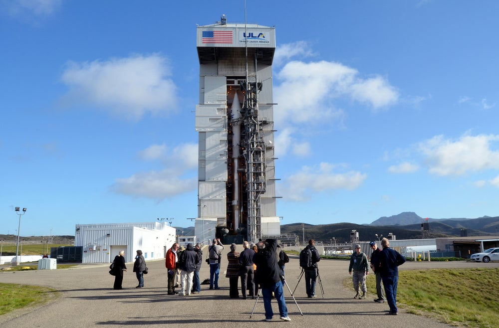 a group of people in front of a metal launch pad for a rocket in california