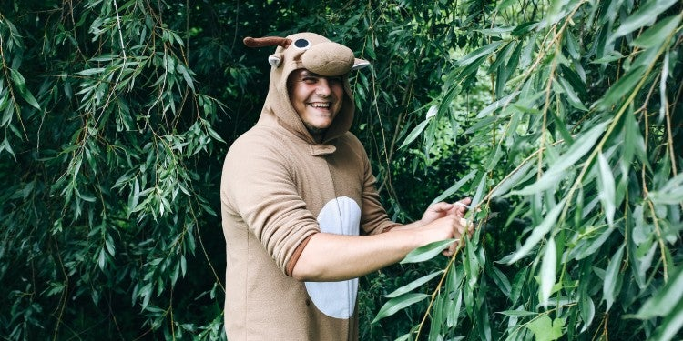 Guy in a deer costume in the forest.