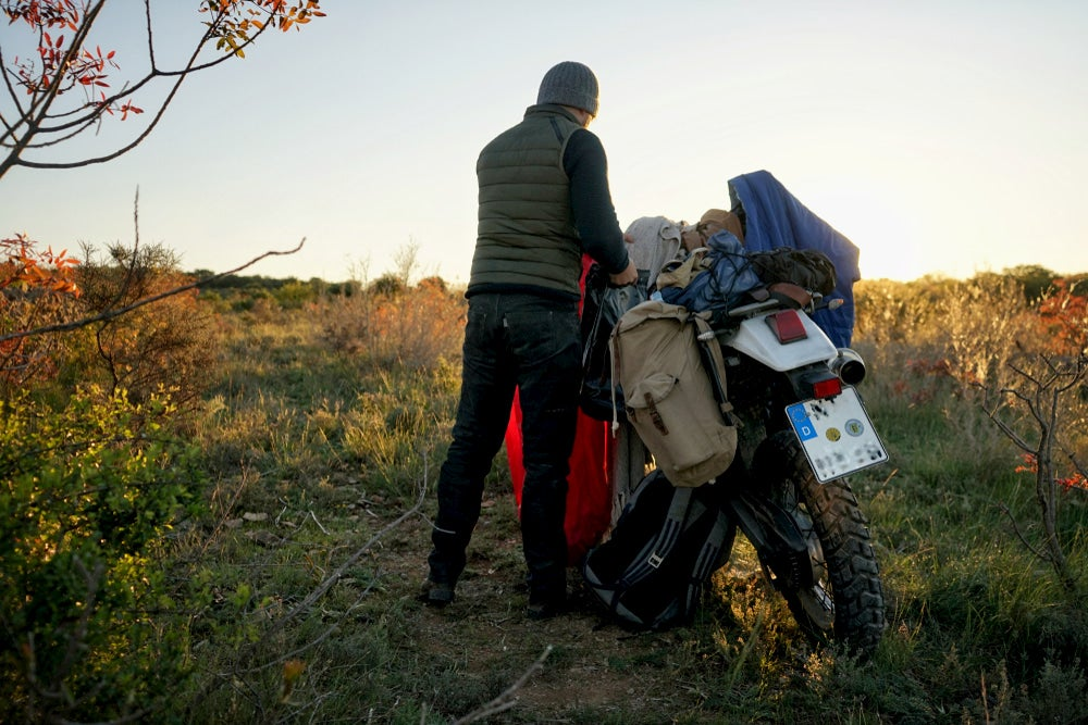 Motorcycle camper packing his pannier bags.