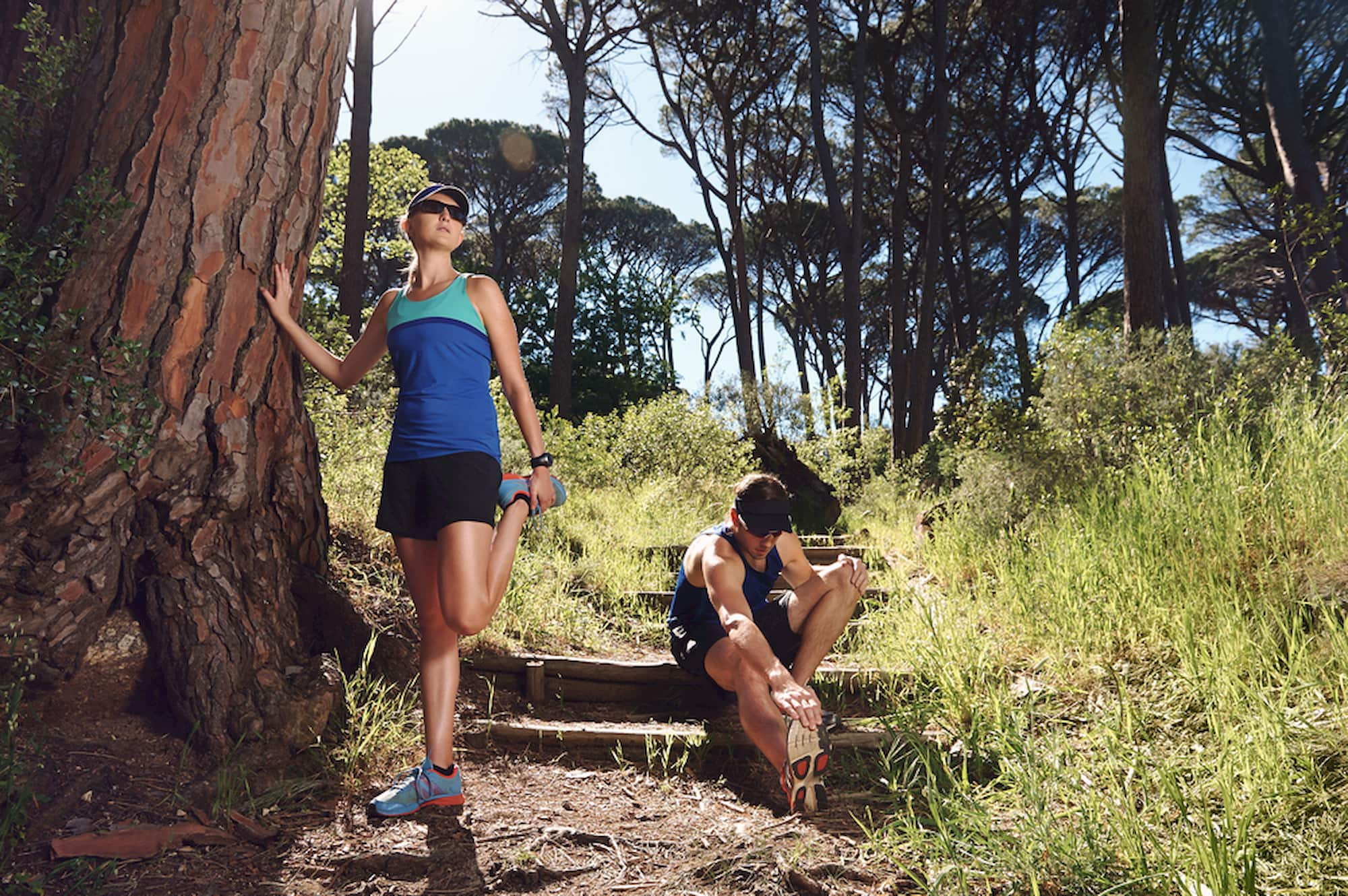 Trail runners stretching on forested trail.