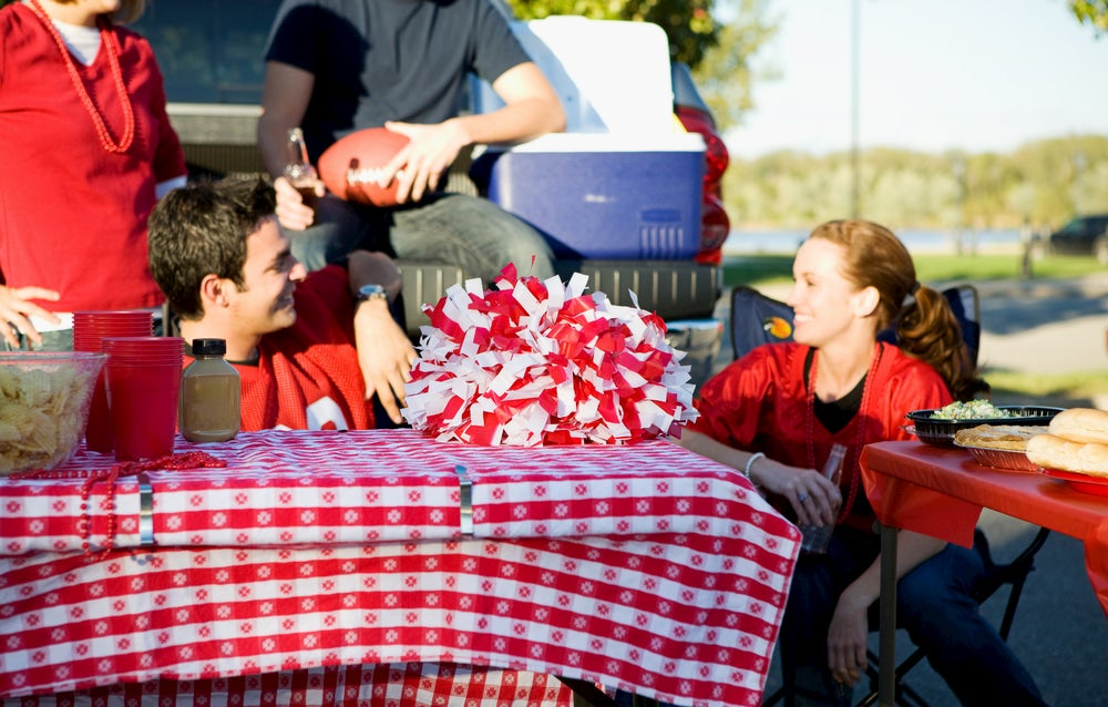 People sitting around table with tailgating supplies.