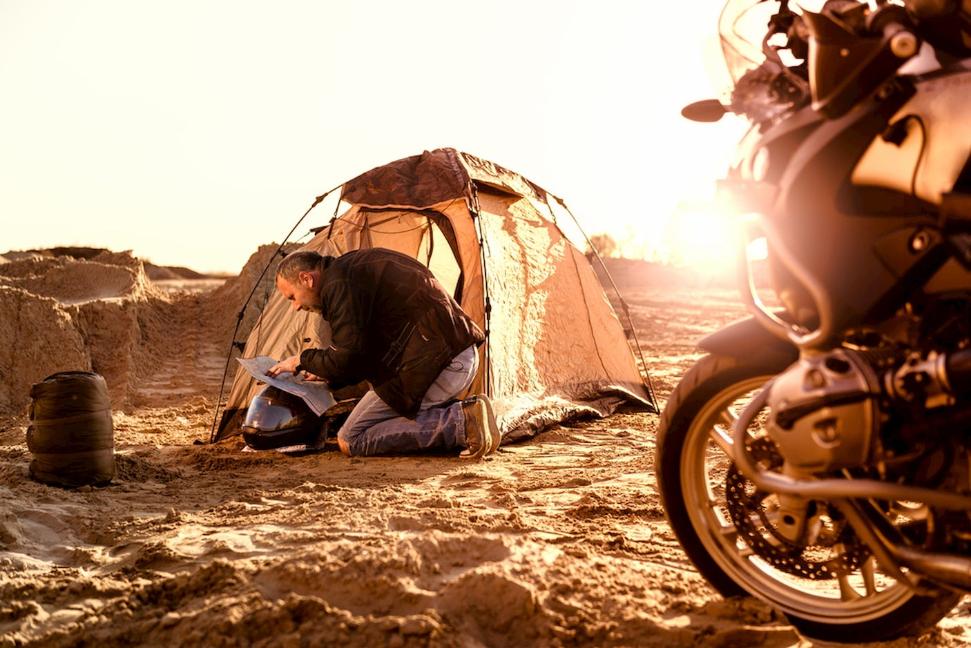 Motorcycle camper packing up tent.