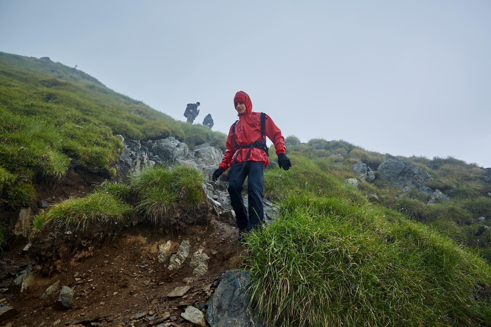 Hikers walking through alpine field in the rain.