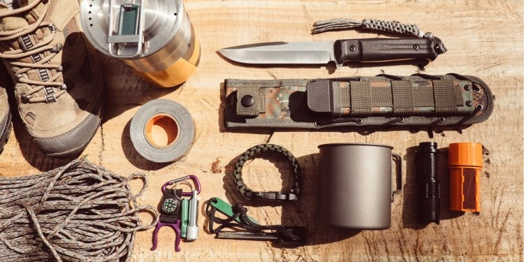 a survival tool gear pack laid out on a log in the wilderness