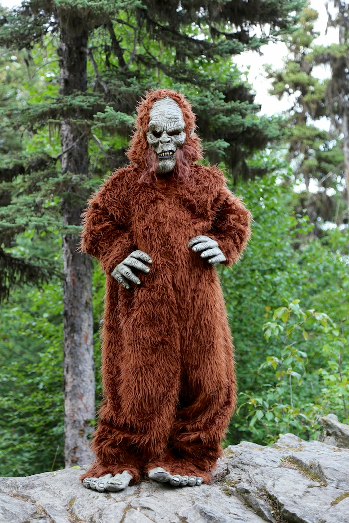 Person wearing sasquatch costume in the forest.