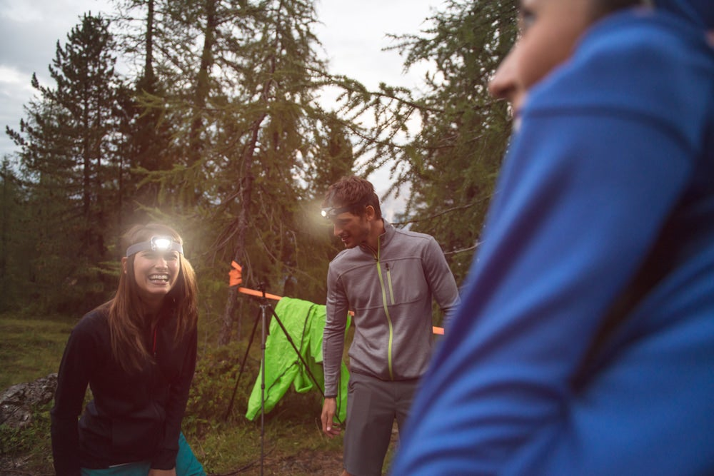 three campers wearing headlamps in the outdoors at dusk