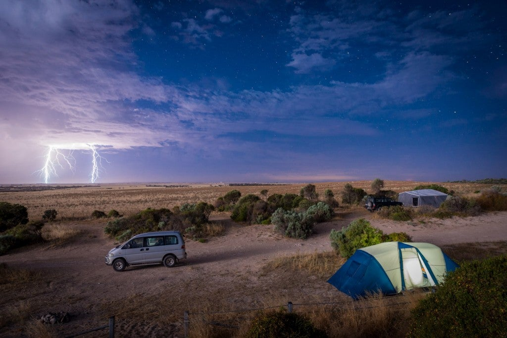 Lightning stirking in a prairie witha tent and van in the foreground.