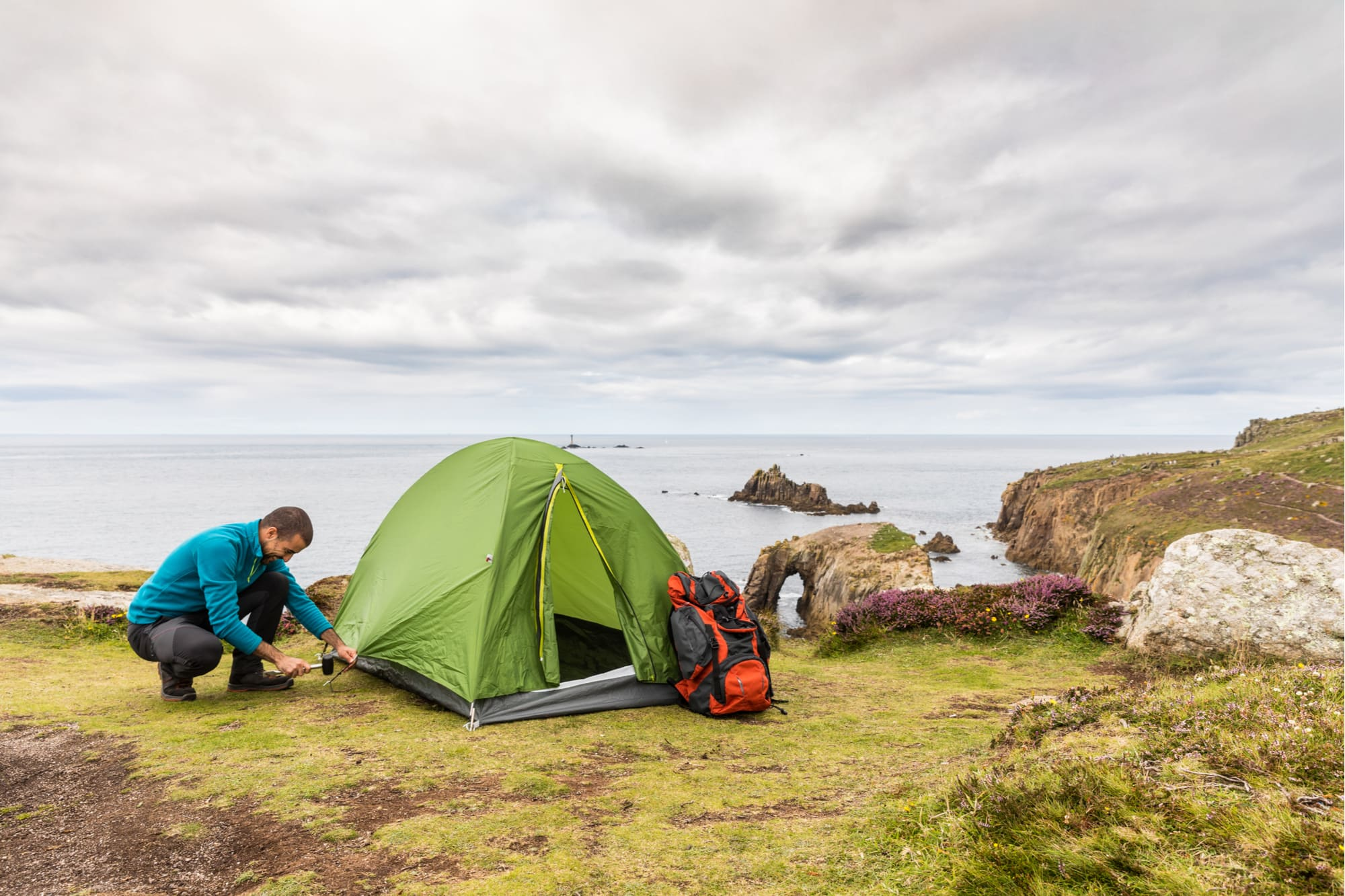 a man pinning down a tent over a cliff